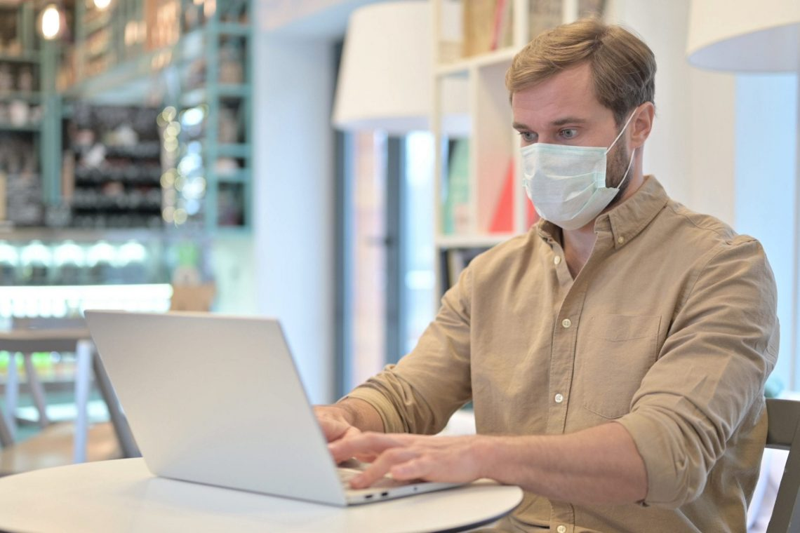 Young Man with Face Mask using Laptop in Cafe