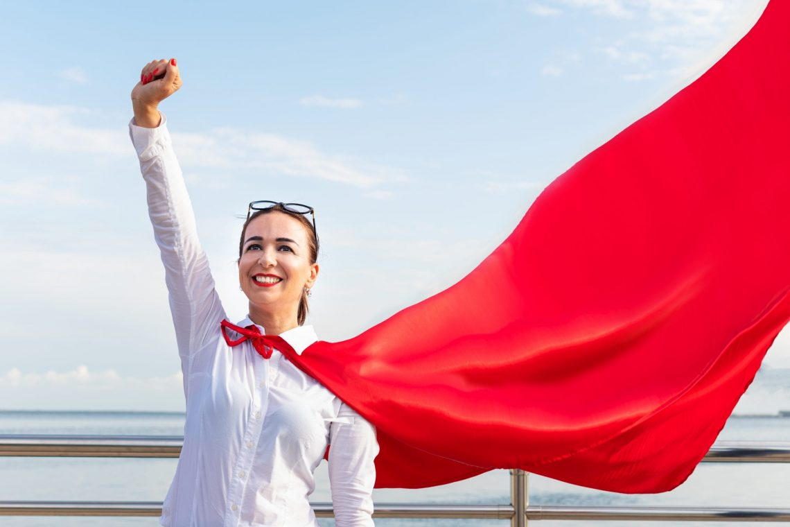 super woman business woman with a red cloak outdoors